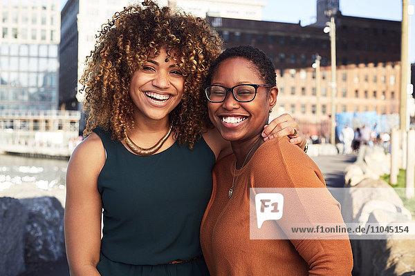 Black women hugging and smiling at waterfront