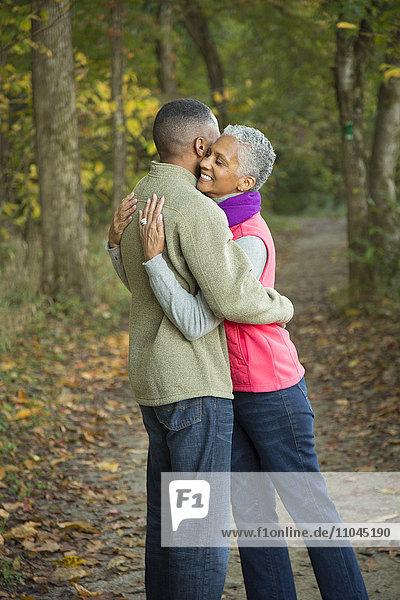 Older couple hugging in forest