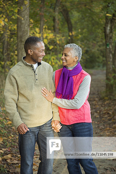 Older couple holding hands walking in forest