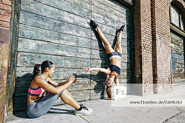 Athlete doing handstand on sidewalk