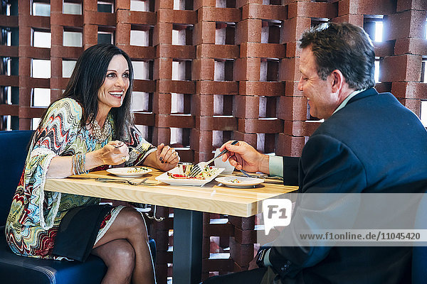Caucasian couple sharing meal in restaurant