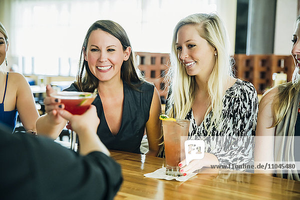Caucasian bartender serving martini cocktail to customer