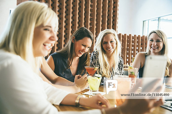 Caucasian women at bar with cocktails taking selfie