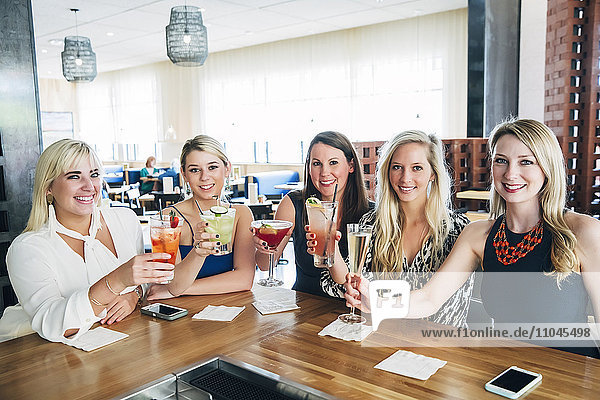 Caucasian women toasting at bar with cocktails