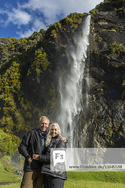 Caucasian couple hugging near remote waterfall