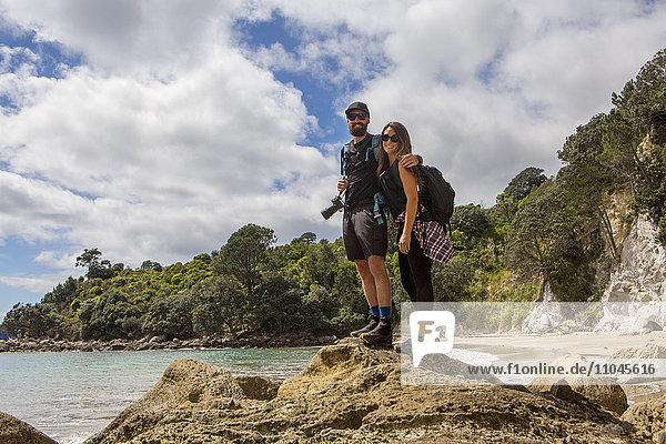 Caucasian couple hiking on remote beach