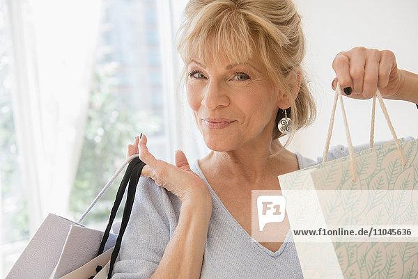 Older Caucasian woman showing shopping bags