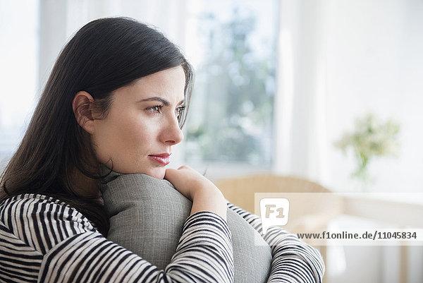 Pensive Caucasian woman clutching pillow