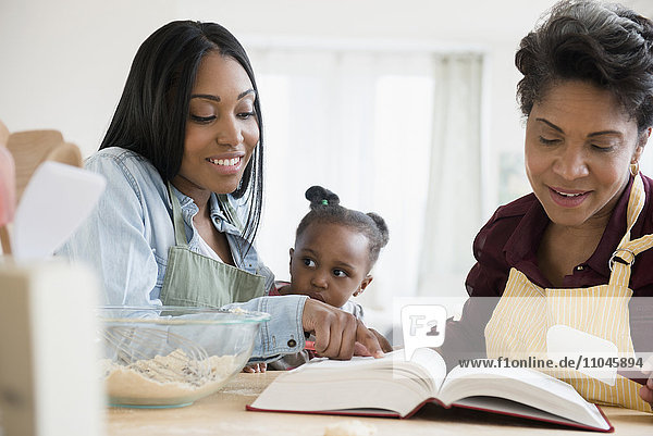 Black multi-generation family reading recipe in cookbook