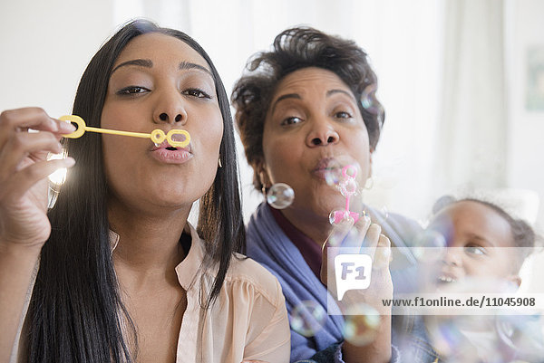 Black multi-generation family blowing bubbles with bubble wand