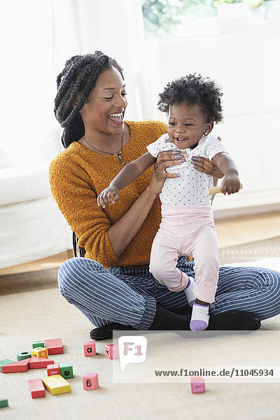 Black mother and baby daughter playing with blocks on carpet