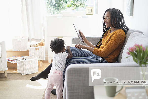 Black woman using digital tablet on sofa near baby daughter
