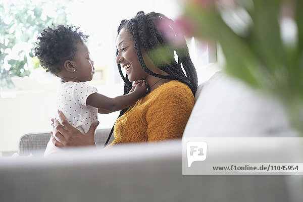 Black woman playing with baby daughter on sofa