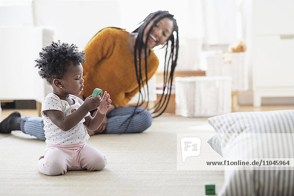Black woman watching baby daughter play with toy on carpet