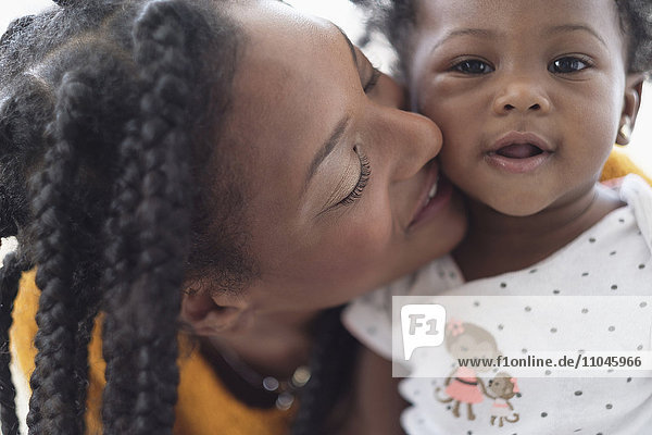 Smiling Black woman cheek to cheek with baby daughter