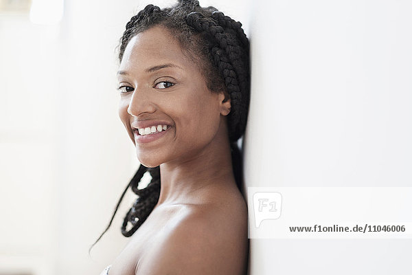 Smiling Black woman leaning on wall