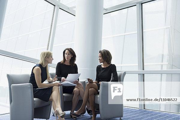 Businesswomen sitting in armchairs talking