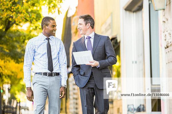 Businessmen walking on sidewalk carrying paperwork
