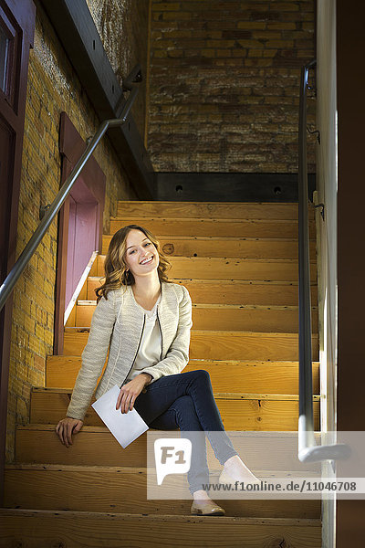 Caucasian woman holding paperwork sitting on wooden staircase