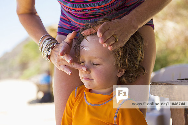 Caucasian mother applying sunscreen to face of son
