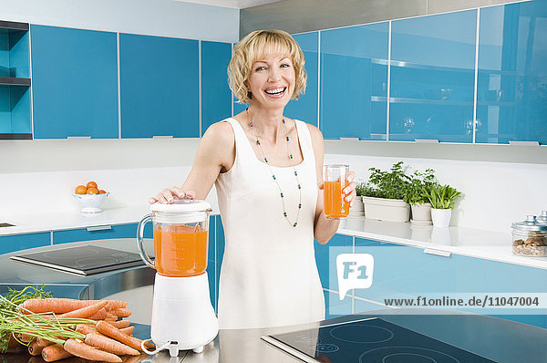 Caucasian woman juicing carrots in kitchen