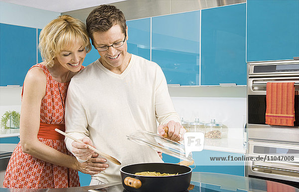 Caucasian couple cooking in kitchen