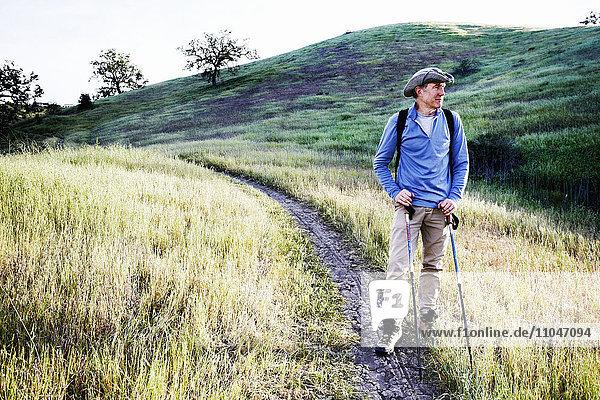 Caucasian man hiking on dirt path on mountain