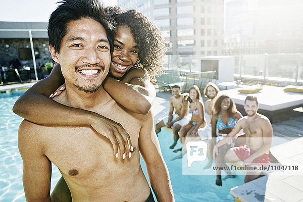 Smiling friends enjoying urban swimming pool