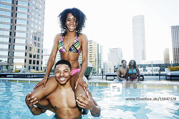 Smiling friends enjoying urban swimming pool