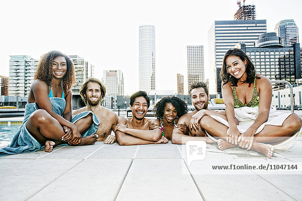 Smiling friends relaxing poolside at urban swimming pool