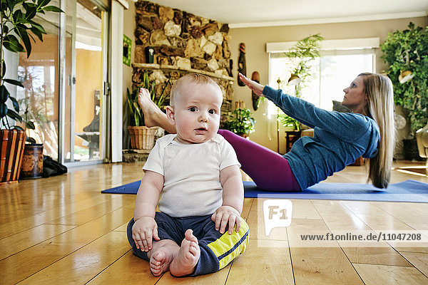 Baby posing on floor while mother exercises