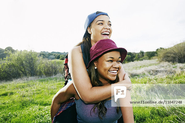 Mixed Race teenager giving sister piggyback ride in field