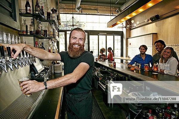 Smiling bartender pouring beer at bar