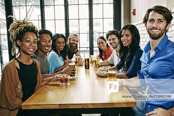 Smiling friends posing at table in bar