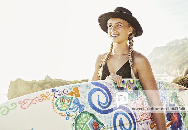 Caucasian woman carrying surfboard at beach