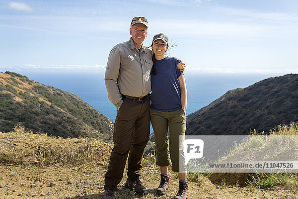 Caucasian man and daughter hugging on mountain
