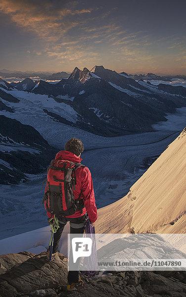 Caucasian man admiring mountain range holding climbing rope
