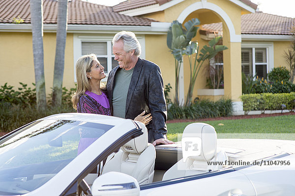 Caucasian couple smiling near convertible
