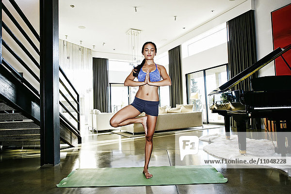 Chinese woman practicing yoga in living room