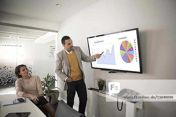 Businessman pointing to charts in meeting