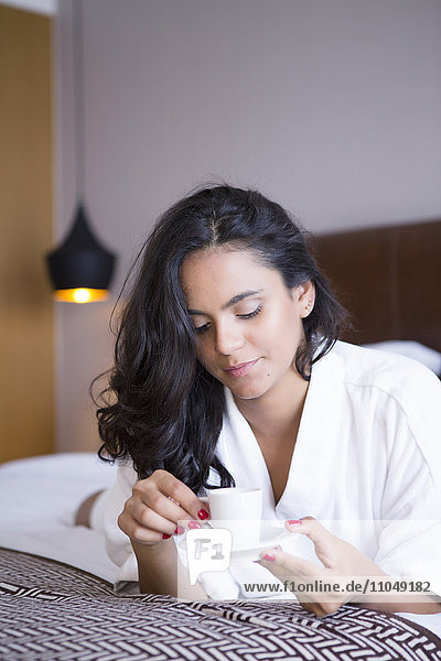 Hispanic woman drinking espresso on bed