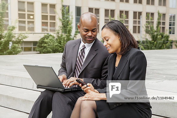 Black business people sitting on staircase using laptop and cell phone