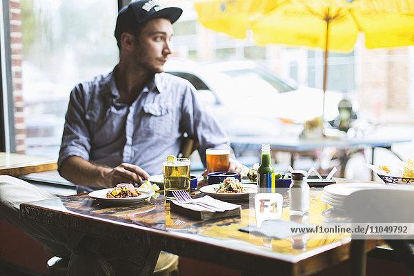 Caucasian man eating tacos in restaurant