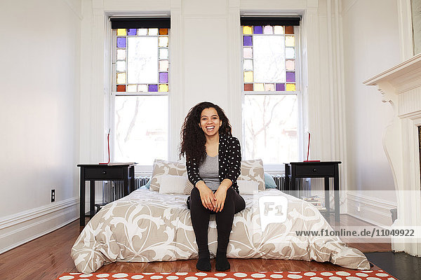 Mixed race woman sitting in bedroom