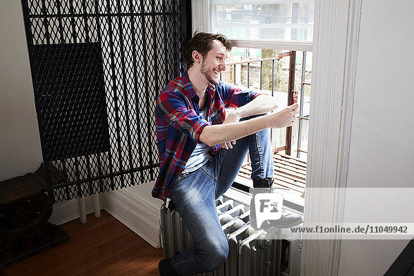 Caucasian man using cell phone in window