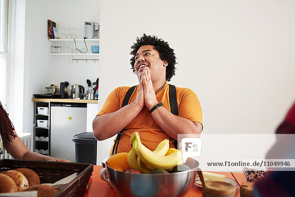 Mixed race man sitting at table and praying