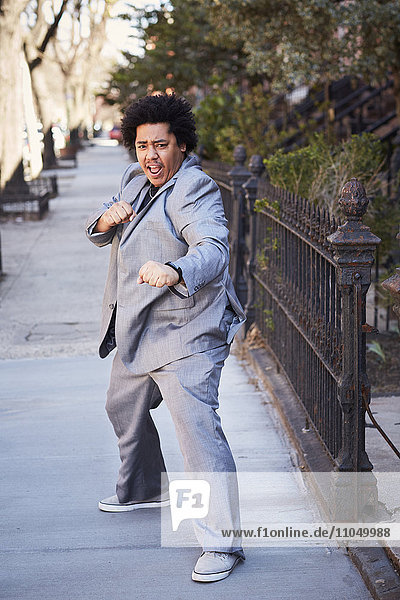 Mixed race man in defensive pose on sidewalk