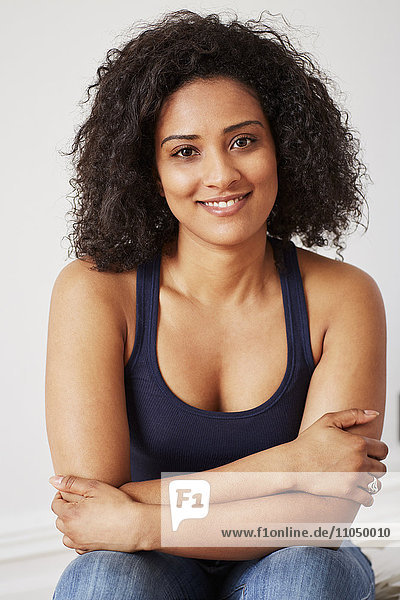 Smiling mixed race woman with arms crossed