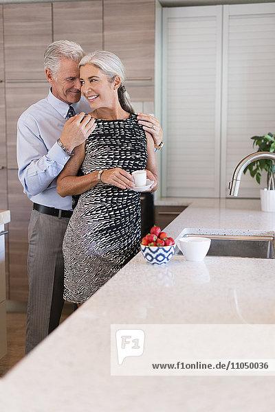 Caucasian couple hugging in kitchen