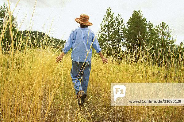 Japanese woman walking in field of tall grass